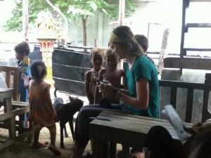 Sara teaches English to the kids.