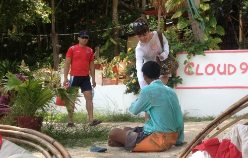 A tourist giving money to a man without legs.